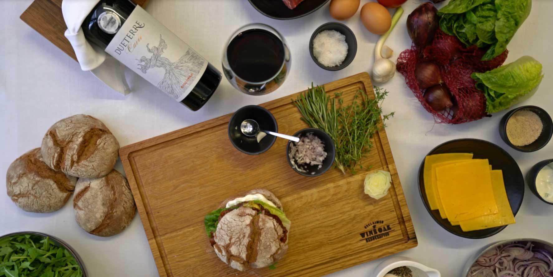 BBQ-Beef Burger mit Sauerteigbrot, Cheddar, gedünsteten Zwiebeln und Rucolasalat